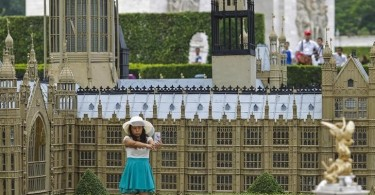 "A woman poses for a selfie in front of a miniature replica of London's Houses of Parliament, at a theme park called ""Window Of The World"" in Shenzhen"