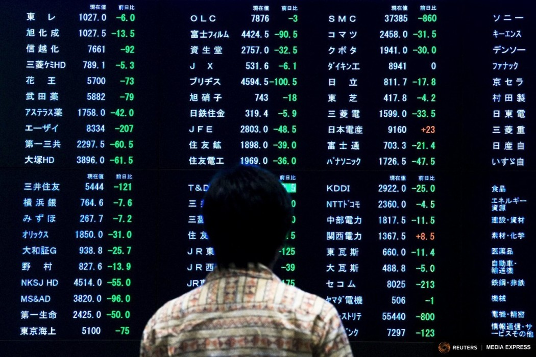 A woman stands in front of a display showing market indices at the Tokyo Stock Exchange (TSE). Photo: Reuters.