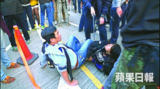 Another officer pointed his baton at Chan. Photo: Apple Daily.