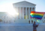 A man holds a rainbow flag in front of the Supreme Court. Photo: Ted Eytan via Flickr.