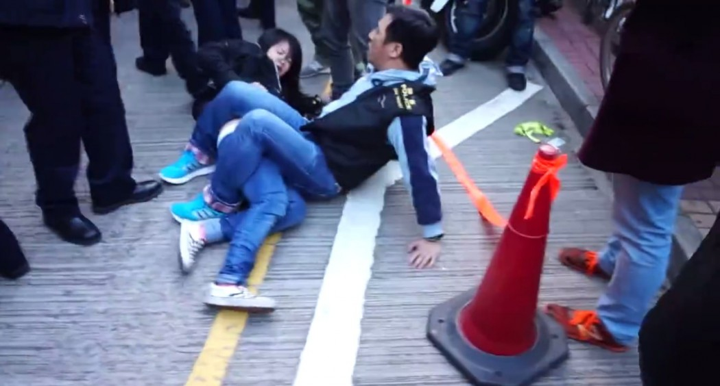 Police clamped his legs over Chan. Photo: Hong Kong Indigenous via Facebook.