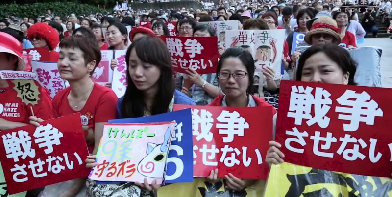 "Protesters in Tokyo hold signs reading ""We will not permit Japan to wage war."" Screencap from 朝日新聞社 (Asahi Shimbun) official YouTube channel."