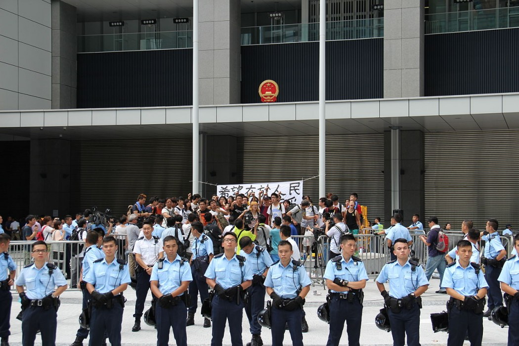 Policemen surround the students protesting at Civic Square