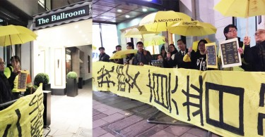 "Protesters in London with yellow umbrella and banner ""I want genuine universal suffrage"" waiting for Leung Chun-ying."