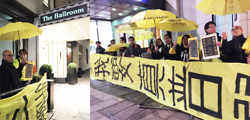 """Protesters in London with yellow umbrella and banner """"I want genuine universal suffrage"""" waiting for Leung Chun-ying."""