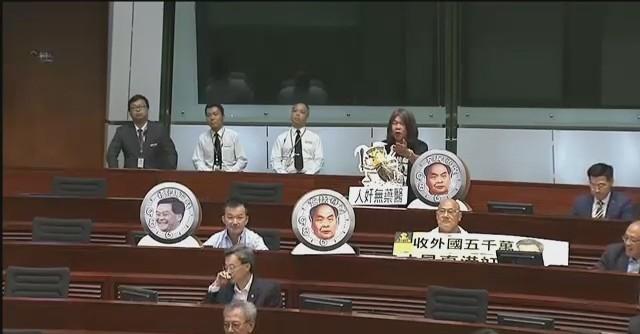 Lawmakers with satirical photos of Leung Chun-ying.