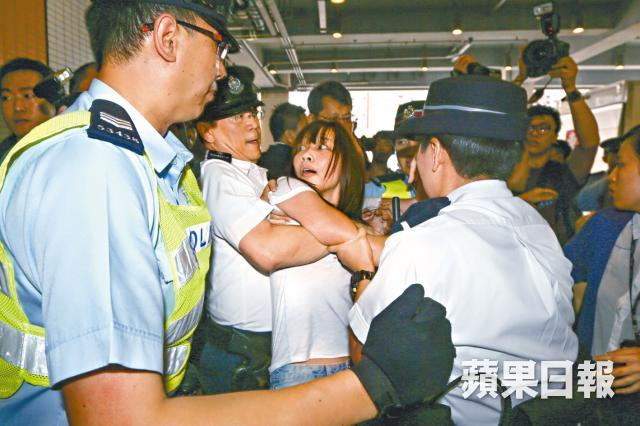 "A female HKFS official being ""bear hugged"" by a male officer. File Photo: Apple Daily."