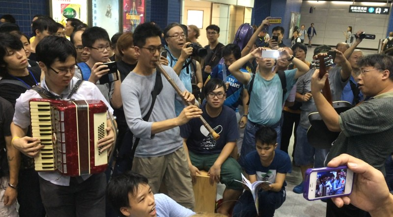 Musicians playing inside Tai Wai station.
