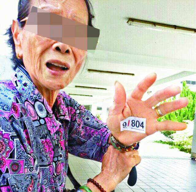 An elderly voter with suspected voting instruction on her hand.