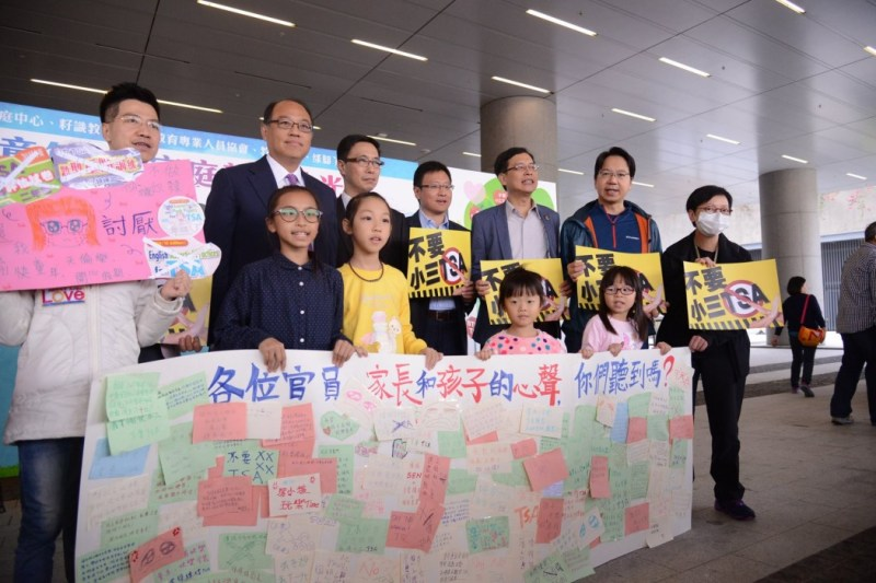 Lawmakers and children protest against TSA exams outside a LegCo hearing on TSA on Sunday.