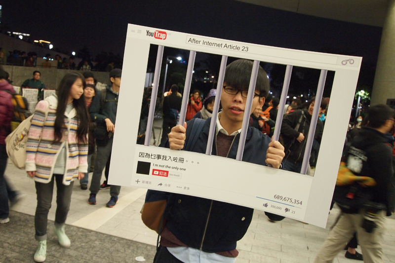 "Scholarism convenor Joshua Wong with a props showing he was ""jailed"" by the new copyright bill. Photo: HKFP."