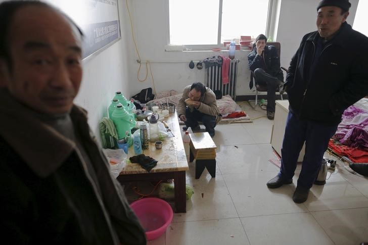 Migrant workers eat breakfast and smoke after waking up at the offices of a subcontractor company. Photo: Damir Sagolj, Reuters.