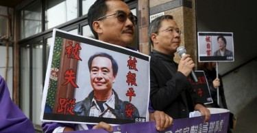 Members from the pro-democracy Civic Party carry a portrait of Lee Bo and Gui Minhai before they protest outside Chinese Liaison Office in Hong Kong