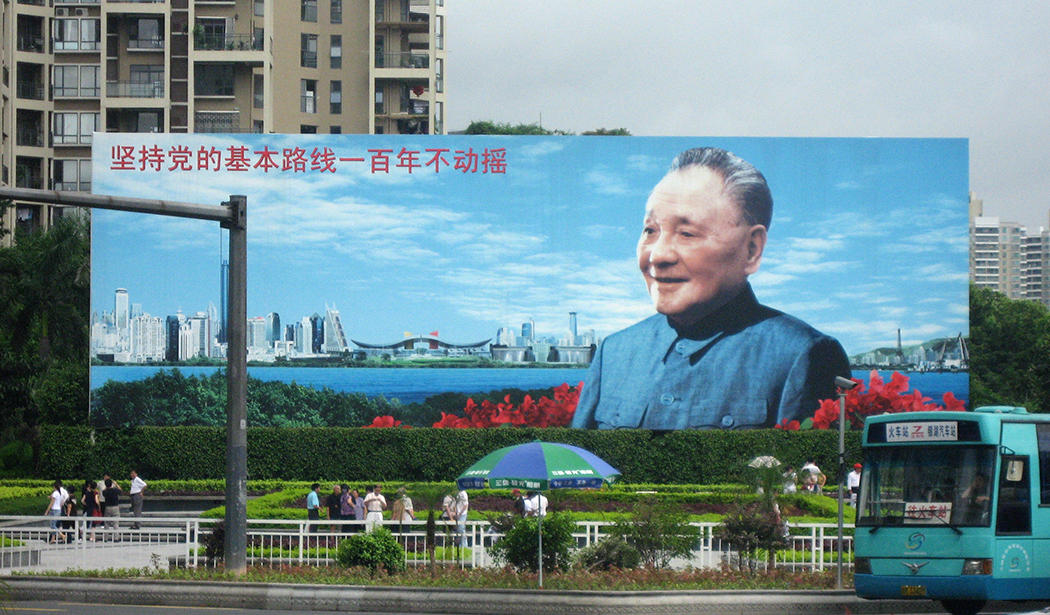 "A billboard of Deng Xiaoping in Shenzhen that reads ""Adhere to the party's basic line for one hundred years with no vacillation""."