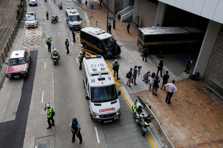 Armed policemen guard the entrance as a prison car carrying British former banker Rurik Jutting enters High Court in Hong Kong