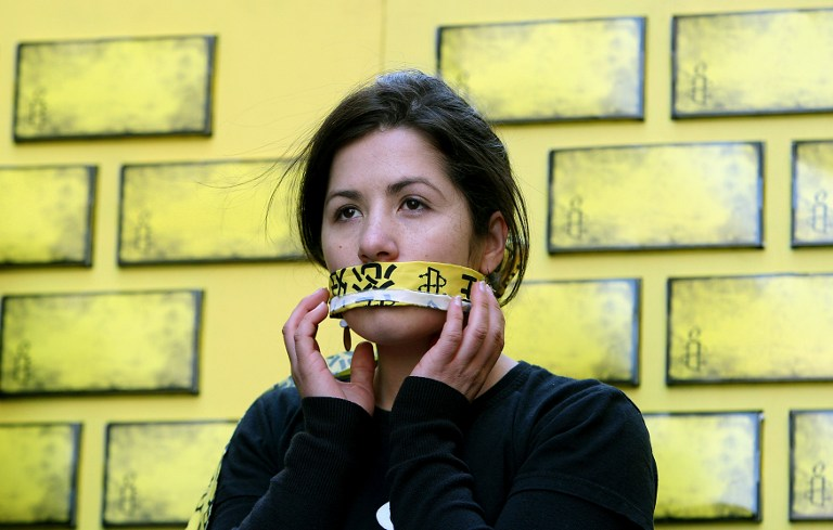An Amnesty International member covers her mouth during an event in Sydney on July 30, 2008 as part of a campaign to end internet censorship in China. Photo: AFP/Greg Wood.