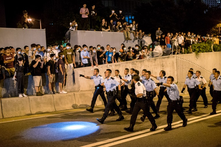 Police officers walk along a road on their way to forcing pro-democracy protesters to move back near the central government offices in Hong Kong on October 16, 2014. Photo: Alex Ogle/AFP.