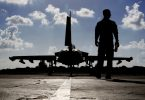 A British soldier walks by a Royal Air Force Typhoon aircraft before it takes off from RAF Akrotiri in Cyprus for a mission in Iraq