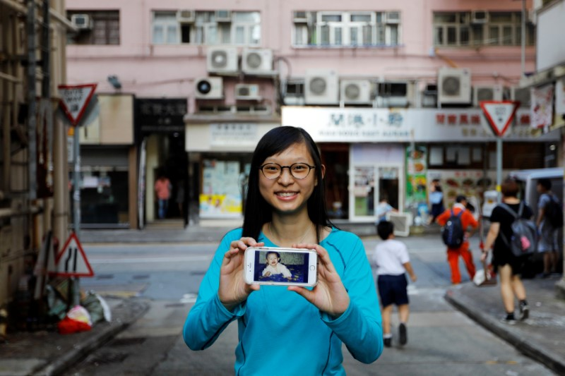 Candy Lau poses with her childhood photo in front of the building in which she was photographed in 1997, in Hong Kong