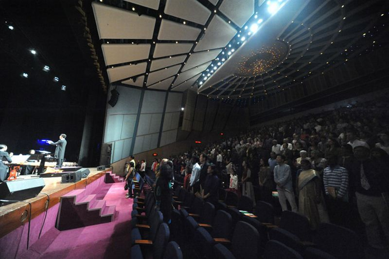 audience stand during the anthem after a concern in Mumbai, 2013. Photo: Wikicommons.