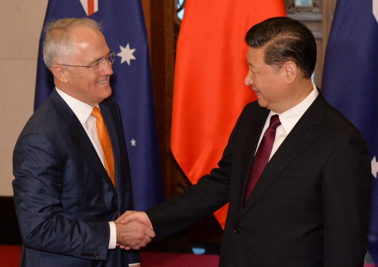 Xi Jinping (R) shakes hands with Australian Prime Minister Malcolm Turnbull