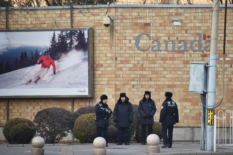 Chinese police officers stand guard outside the Canadian embassy in Beijing