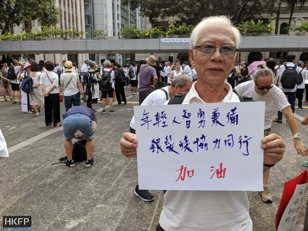 "Mr. Wong, a retired repairman, joined the march holding a sign that reads: 'Young people have both intelligence and bravery, the silver-haired will walk with you."" Photo: Holmes Chan/HKFP."
