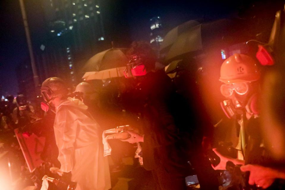protesters night gear gas masks umbrellas poly-u