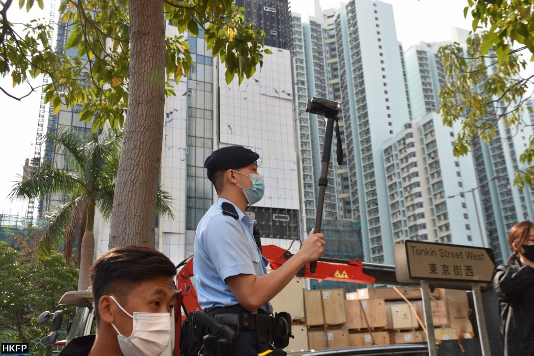 Police officer recording people chanting slogans