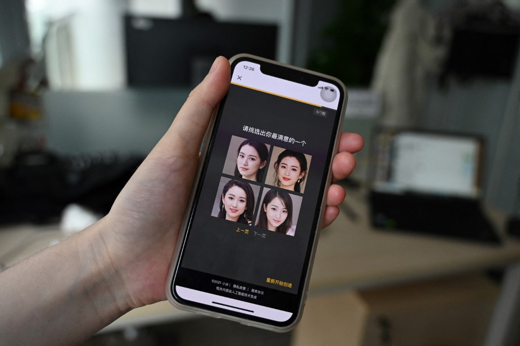 This photo taken on July 5, 2021 shows a staff member displaying AI-generated faces which can be selected as virtual girlfriends created by XiaoIce, a cutting-edge artificial intelligence system designed to create emotional bonds with its 660 million users worldwide, at the company's office in Beijing.
