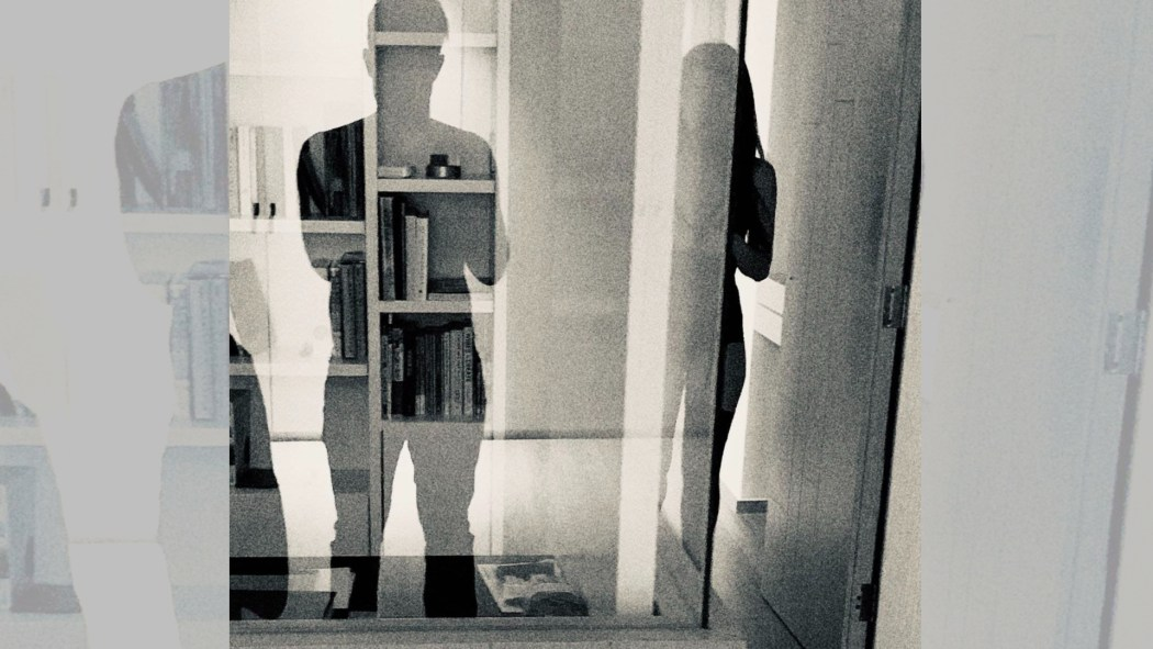Leonard and Salome photograph their own silhouette in front of a reflective glass pane.